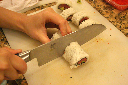 Trying to cut even slices. You have to do a sawing motion with the knife to cut the roll, so that it doesn't squash it.