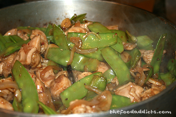 Together with the previous ingredients, we also added snow peas. Stir-fry all the vegetables first, then throw in the chicken pieces. Cook that for a few minutes before adding the Kung Pao sauce. Continue cooking and stirring until the chicken is cooked through.
