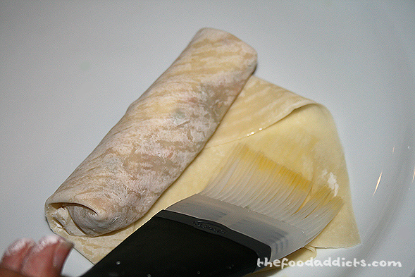 Roll tightly up and use a beatened egg to seal the wrapper.