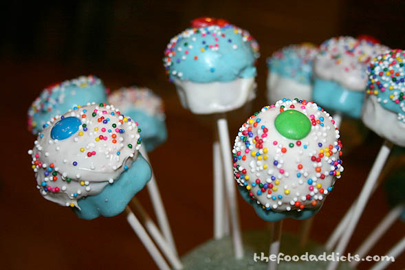 With the top still wet, take an M&M candy and stick it in the center and add sprinkles on top. Then place the sticks upright (here we used a styrofoam ball) and let the top dry completely.