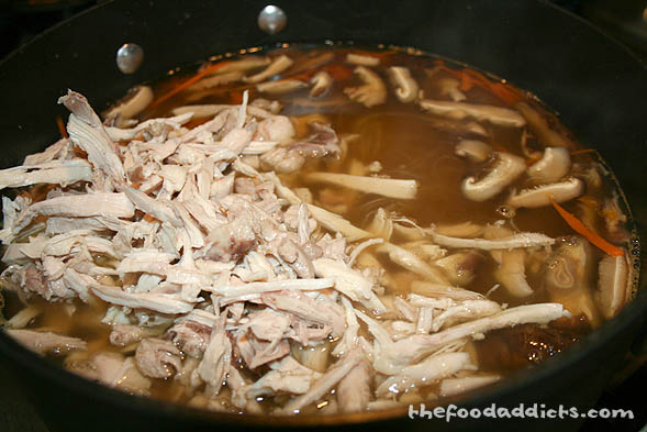 While prepping your ingredients, pour in four 14 oz. cans of chicken stock in a large pot and bring to a low boil. Then add the carrots, shitake mushrooms, ginger, and shredded chicken (or any other meat you prefer) and let it cook a few minutes. Season the soup with 1 tbsp soy sauce and 1 tsp sesame oil. Finally, add the bean thread noodles and cook through until soft.