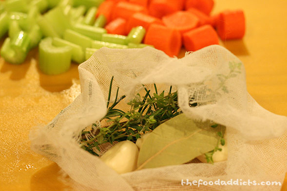 First, chop up 1 small onion, 1 carrot, and 1 celery stalk. Next, place a sprig of rosemary, thyme, 1 bay leaf, and a couple cloves of garlic into cheesecloth and tie it up - this is the herb bouquet that will go into the pot for braising.