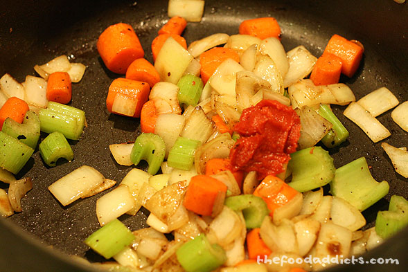 In the same pot, saute the onion, carrots and celery. Season with salt and cook until soft, about 8 minutes. Then add 1 tbsp of tomato paste and mix well.