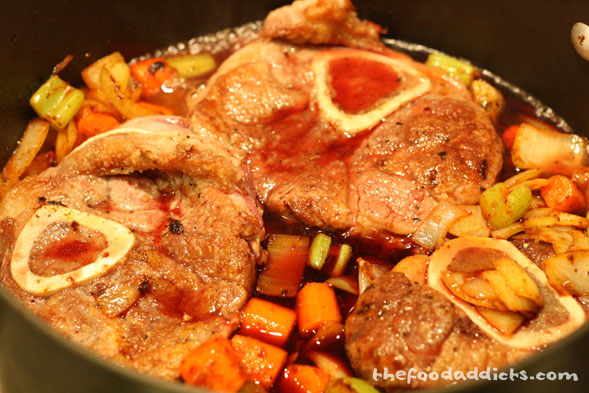Return the browned shanks to the pot and add 1 cup of red wine (Giada used white wine, but we changed it up). Once the liquid reduces by half, add the herb bouquet and 2 cups of veal demi glace (use chicken stock if you don't have it) and bring to a boil. Reduce to low heat, cover, and simmer for about 2 hours or until the meat is tender.