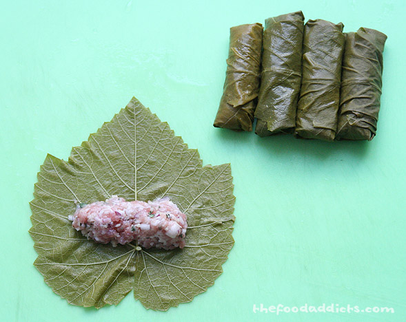 We took a blanched grape leaf and placed about a tbsp in the center. Next, we folded the stem end over the filling, folded in the edges of both sides, and wrapped it up. This is like rolling an eggroll!