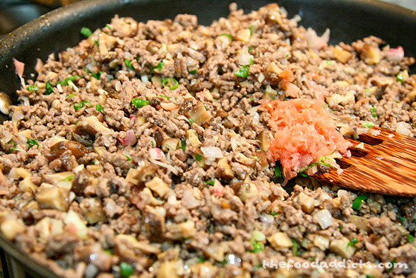 In a large pan, brown 1-1.5 lbs of ground beef and drain excess fat and liquid. Next, combine the shallots and garlic and cook for a few minutes, then add the shiitake mushrooms, pickled ginger, green onion, and Thai chilies. Now pour in the sauce (1 tbsp Hoison, 1 tbsp soy sauce, 2 tbsp Oyster sauce, 1 tsp sugar, 2 tsp cornstarch, 1 tbsp rice wine vinegar, 2 tsp sesame oil). Taste and adjust seasonings to your preference. When everything's good, turn off the heat and toss in the glass noodles (since it's already cooked and you don't want to get it soggy). Note: Printable Recipe below!