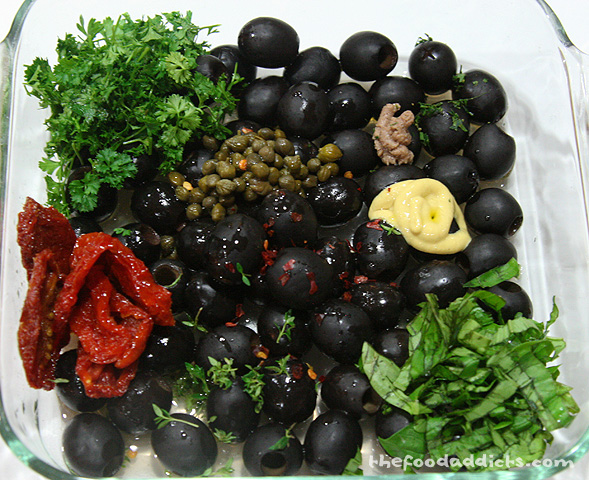 The ingredients we used for this recipe are: 12 oz. of black olives (it's best if you use Kalamata), 2 tbsp capers, 1 tbsp anchovy paste, 2 tbsp sun-dried tomatoes, 1 tbsp Dijon mustard, 1/2 lemon juiced, 1 tsp red wine vinegar, 2 tbsp fresh chopped parsley, 2 tbsp fresh chopped basil, 1/2 tsp fresh thyme, 1 finely chopped bay leaf, and 1/4 tsp crushed red pepper.